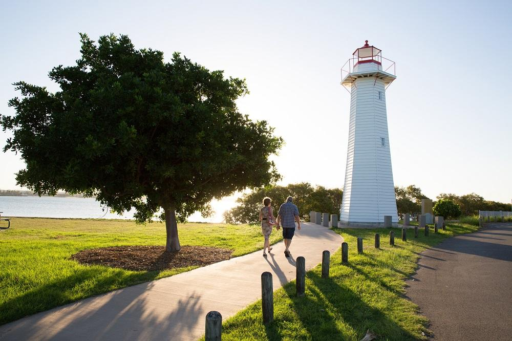 Photo of Cleveland Point Lighthouse with older couple holding hands